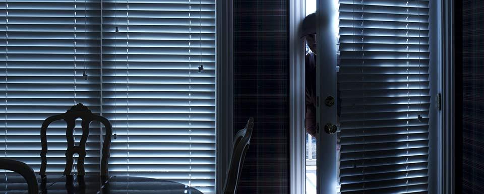 Ladrón colándose por una puerta abierta de la casa
