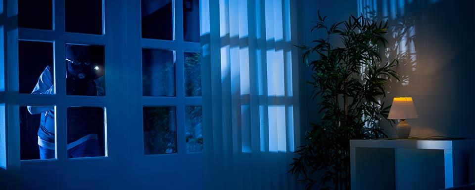 Ladrón con linterna esperando colarse en casa